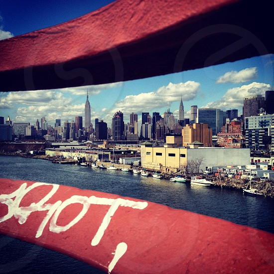 waterfront city skyline through red boat railing with white graffiti photo