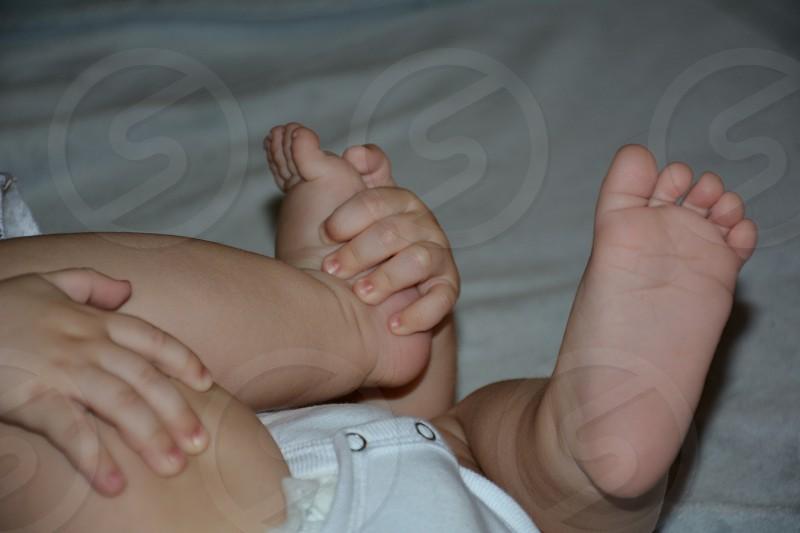Baby yoga! Tiny infant hands clutching tiny baby feet photo