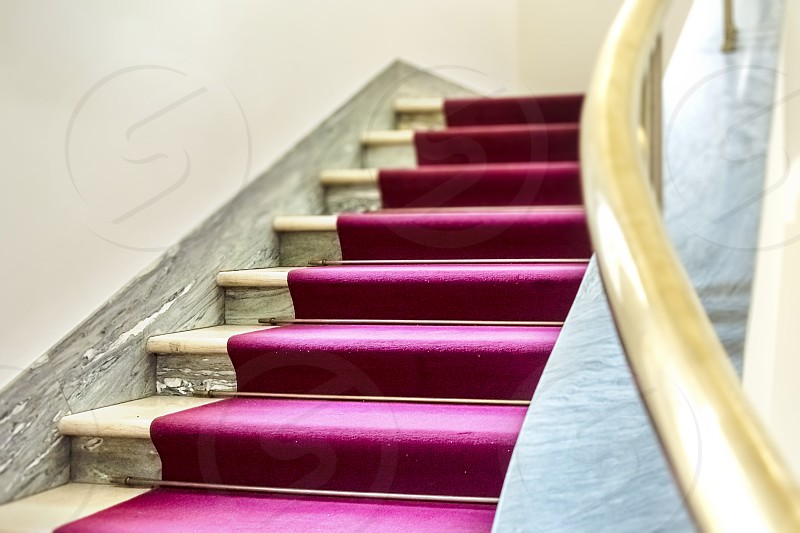 elegant staircase with a purple velvet carpet on the steps and a brass handrail. Elegance and luxury. Events and awards photo