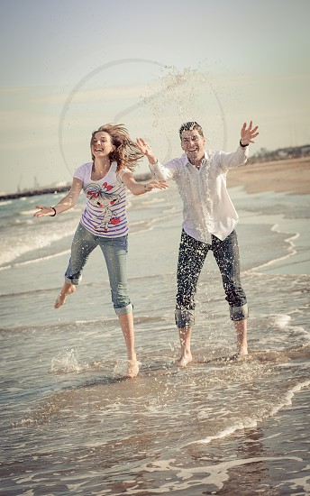 beachfront with man in white button down shirt and woman wearing white striped t shirt photo