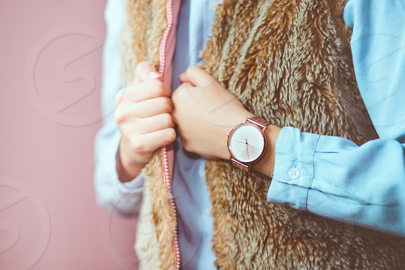 Young woman wearing pink gold wristwatch brown sheepskin vest and blue blouse. Standing in front of pastel pink wall photo