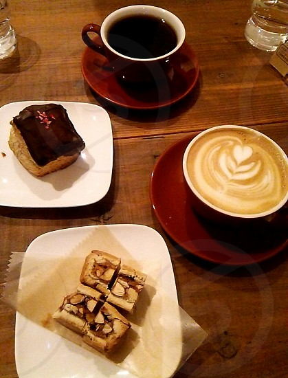 two cup of coffees and pastries on brown wooden table photo