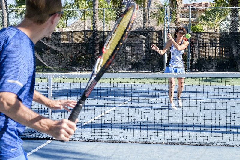Senior citizens playing tennis at a court photo