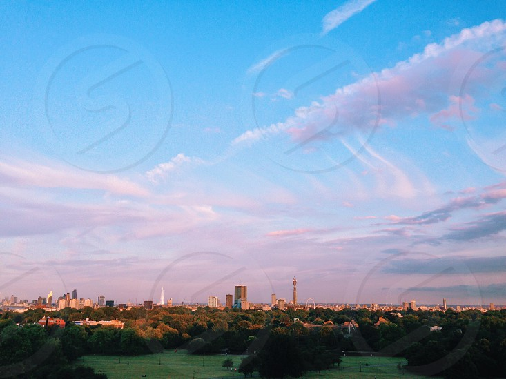 white cumulus clouds over the city photo