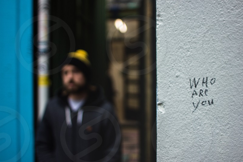 shallow focus photo of who are you text near man in black zipped jacket and knit beanie cap photo