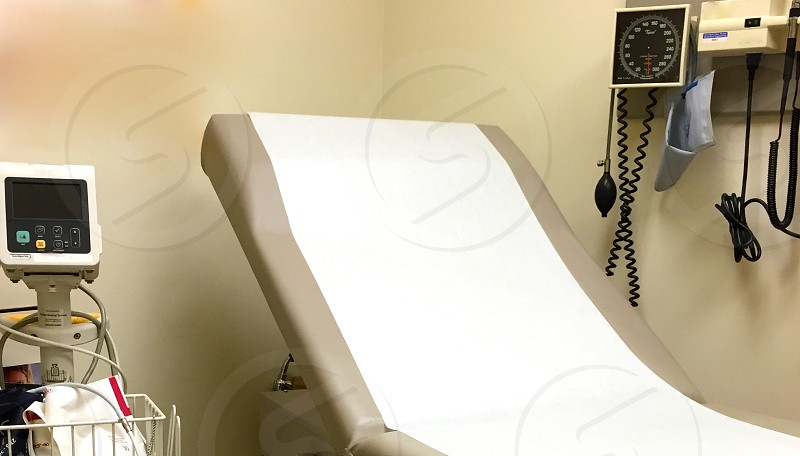 white and brown hospital bed beside wall mounted sphygmomanometer and beige medical device photo