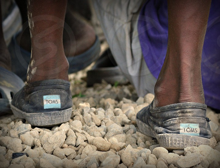 """Given"" A boy wears his worn Toms shoes that he was given around the rocky terrain. photo"