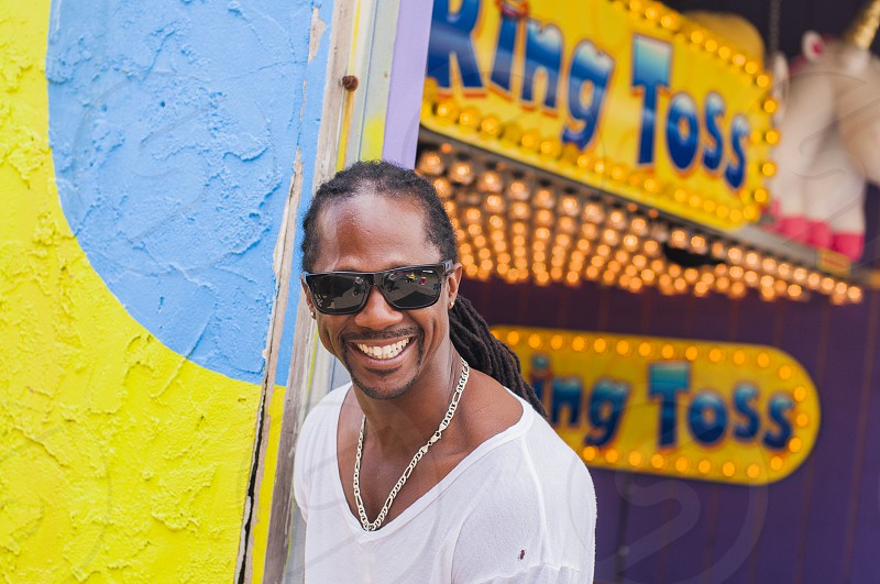 man wearing black sunglasses and silver chain necklace and white shirt smiling against blue and yellow wall of king toss building during daytime photo