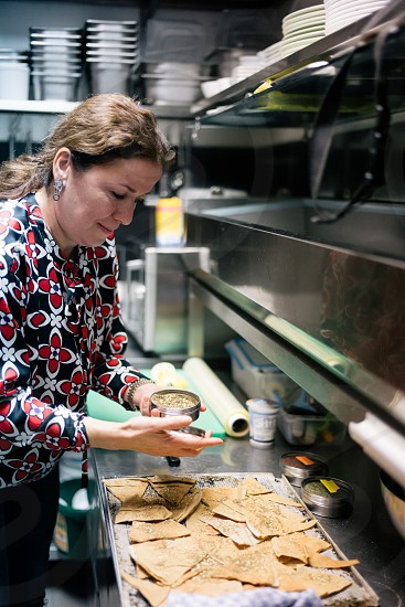 A food entrepreneur prepares Mediterranean dishes in the cafe kitchen before launching her event.  photo