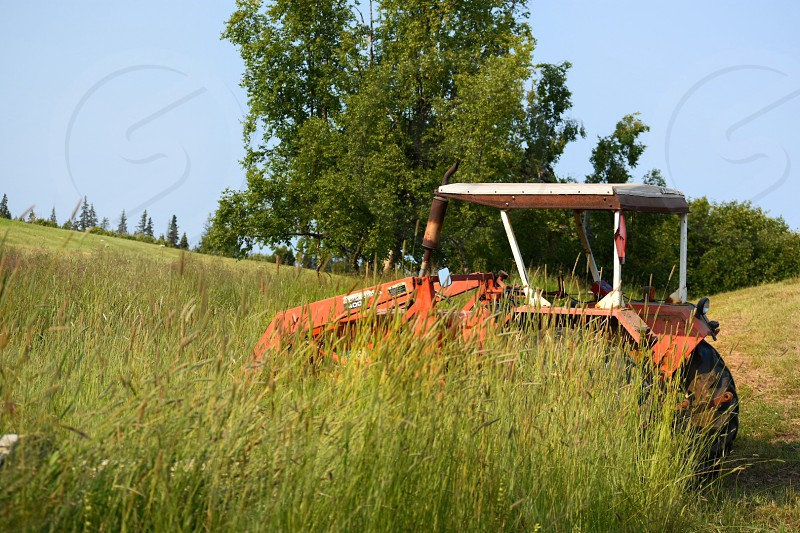 A red tractor parked in a hayfield on a summer day photo