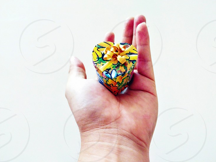 yellow black blue green and orange heart mini box with yellow ribbon on person's palm photo