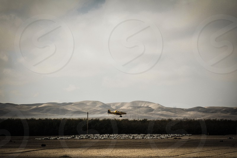 airplane flying over runway area next to mountains photo