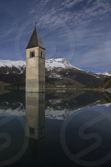 South Tyrol Italy. The lake Resia (italian: Lago di Resia german: Reskensee) is famous for the steeple of a submerged 14th-century church; when the water freezes this can be reached on foot. A legend says that during winter one can still hear church bells ring. In reality the bells were removed from the tower on July 18 1950 a week before the demolition of the church nave and the creation of the lake for a dam's construction. photo