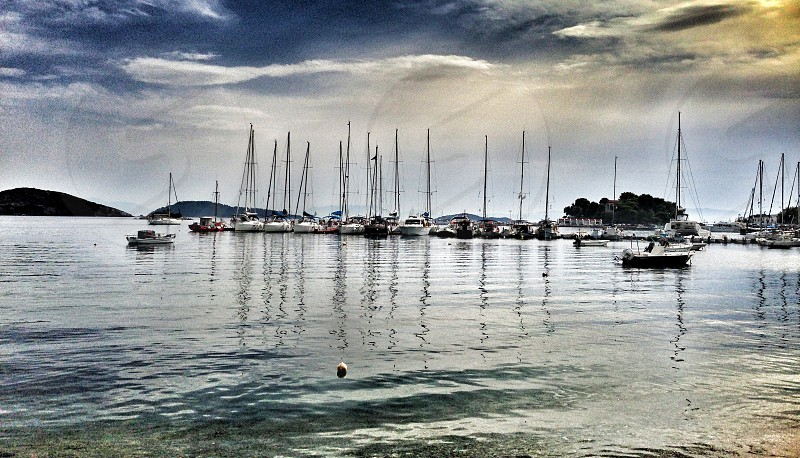 boats on calm water under cloudy sky photo