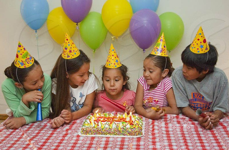 Native American children's birthday party is celebrated with a decorated cake candles ballons horns and hats photo