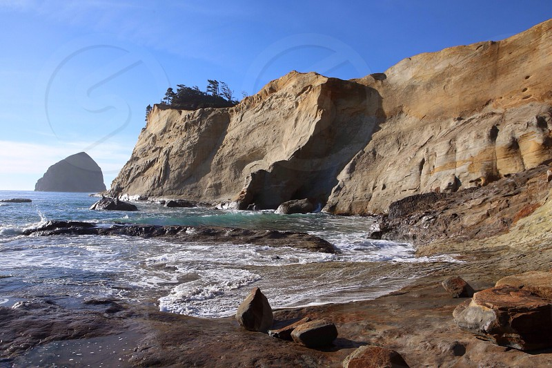 brown rock formation on sea shore photo