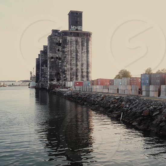 water near warehouse boxes and old buildings photo