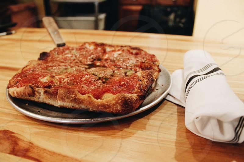 pizza on black pan beside white table napkin on table photo