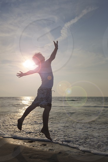 boy jumping in the sea on a sunny day photo