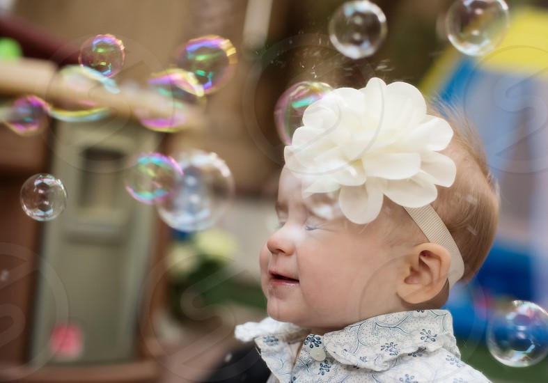 Bubbles popping on baby's face eyes closed. photo