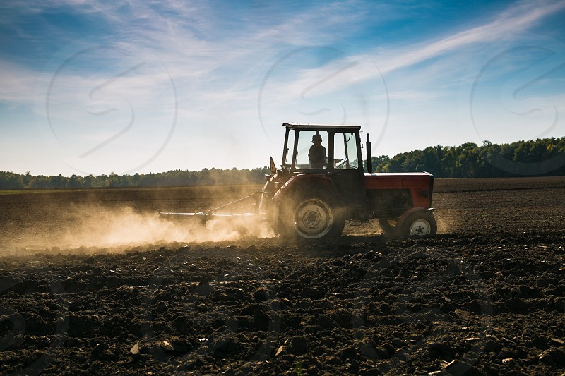 person in tractor in open field with trees in distance photo