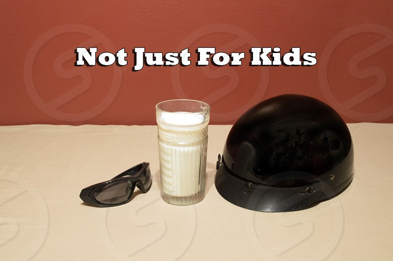 "Glass of milk with motorcycle helmet sunglasses and saying ""Not just for kids."" photo"