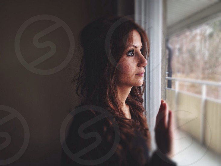 woman in black shirt leaning on a window glass photo