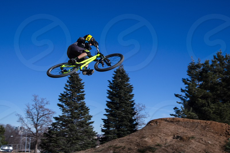 Bicyclist performing jumps off ramps at Ruby Hill Terrain Park Denver Colorado photo