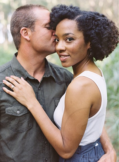 woman in white tank top being kissed by man in dark grey button down shirt photo