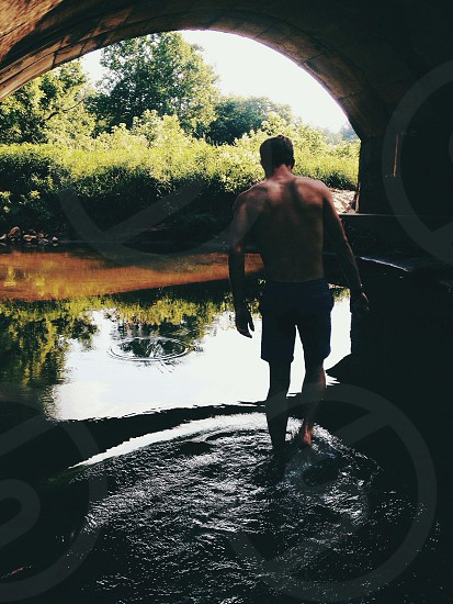man wearing blue shorts walking on a river photo
