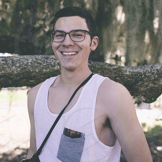 male smiling with black rimmed glasses photo