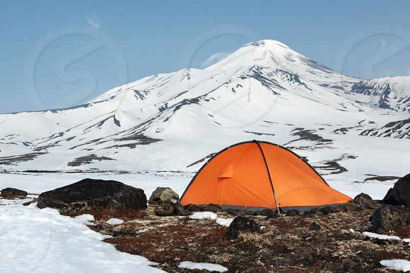 Orange tourist tent standing on meadow surrounded by snow on background of scenic volcanic cone of Avachinskaya Sopka. Russia Far East Kamchatka Peninsula Avachinsky-Koryaksky Group of Volcanoes. photo