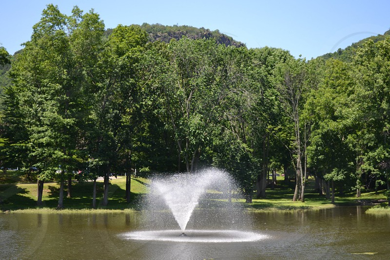 view of the fountain showering on the lake in the forest photo