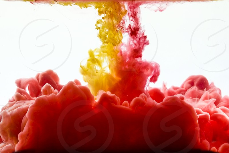 Red and Yellow ink splashing in the water photo