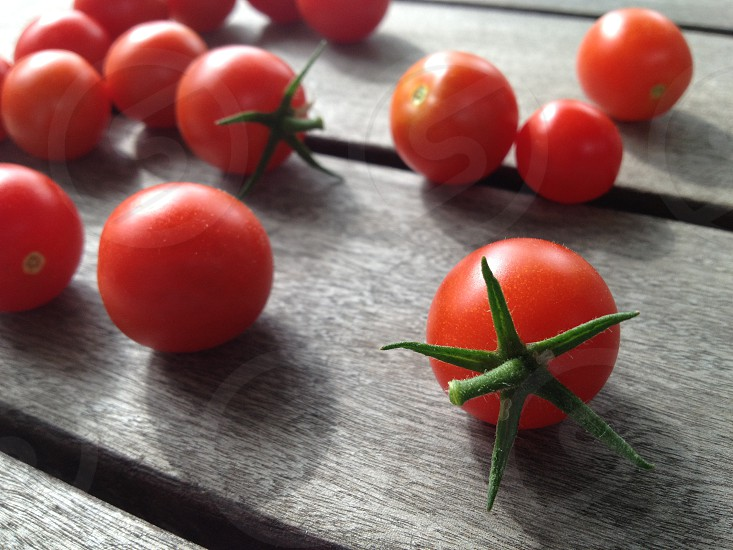 red round chrry tomatoes on wooden table photo