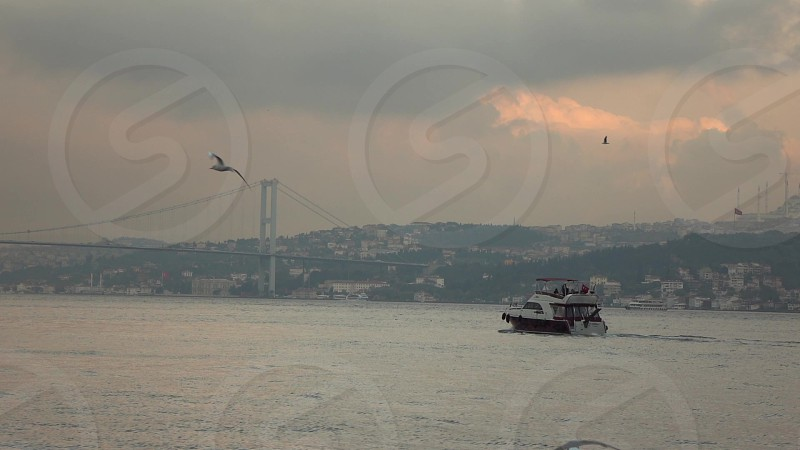 Landscape of views of Istanbul with tourist ship in Bosphorus strair and 15 July Martyrs Bridge on a background of sunset cloudy sky. photo