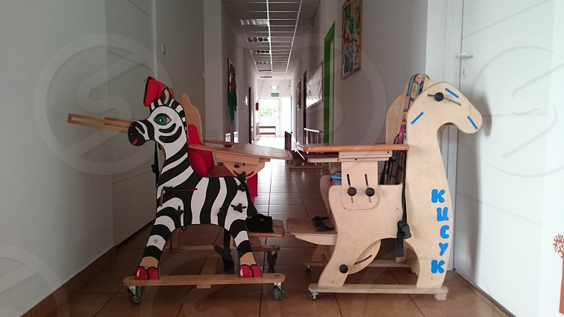 two zebra and horse rolling highchairs on hallway photo