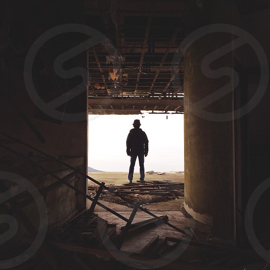 man silhouetted near ruined building portrait photo