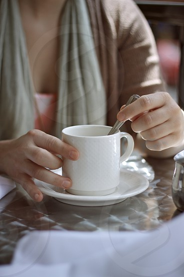 cafe coffee cup drink hands money mug spoon stainless steel table stir white woman photo