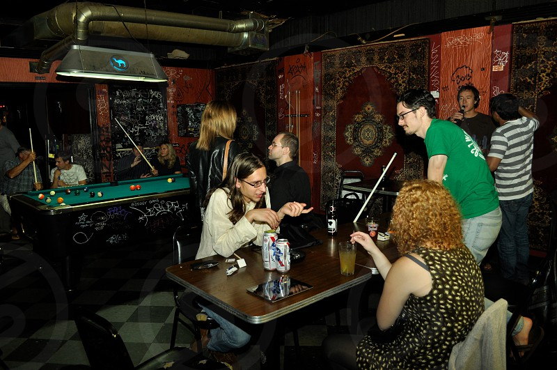 people sitting on a bar with billiards table photo