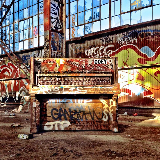 brown wooden upright with graffiti photo