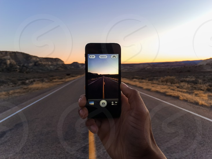 black iphone taking picture of road photo