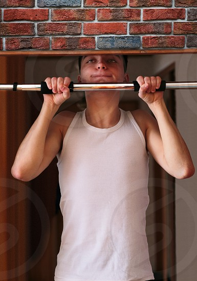Young man executing exercise pulling up on horizontal bar at home. Portrait orientation photo