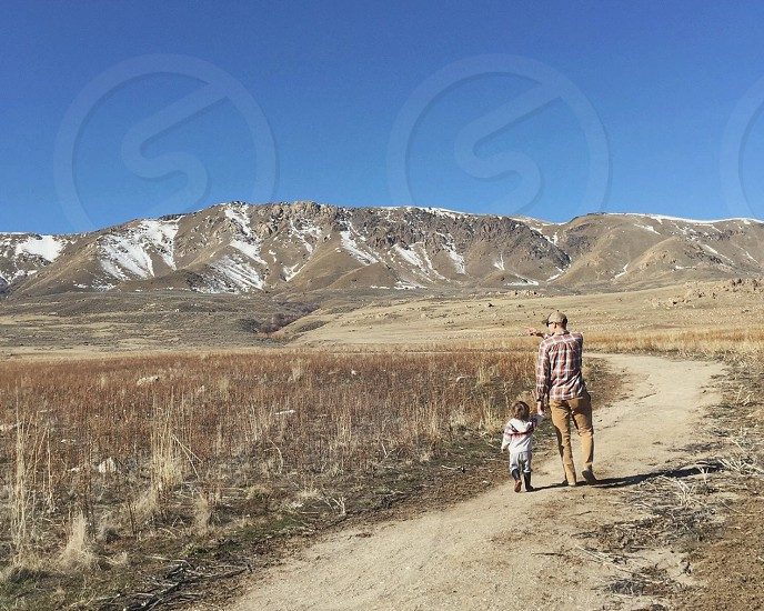 Father and son walking along trail toward mountain peak on antelope island in north Utah on the great salt lake. Father pointing toward herd of free range bison grazing along the snow tipped mountains.  photo