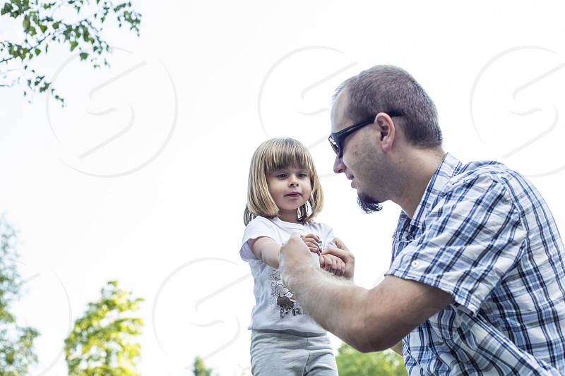 man in blue and white checked button up t shirt holding of girl hand standing during daytime photo