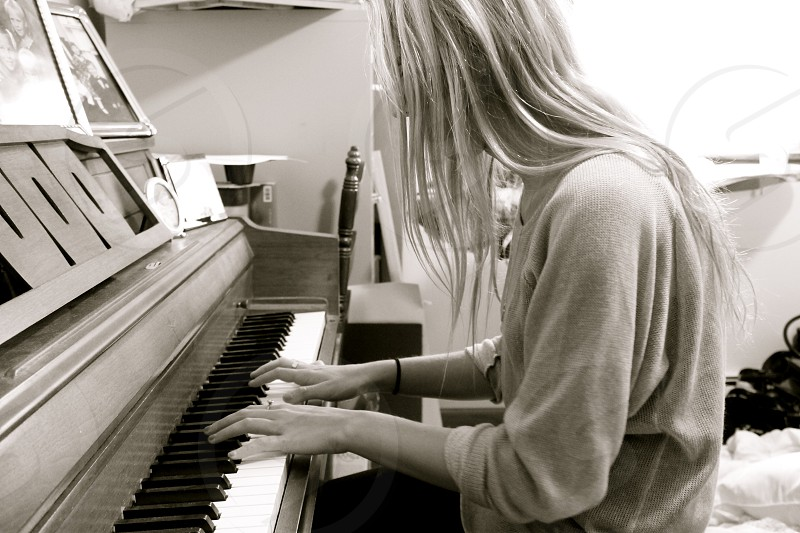 woman playing piano gray scale photography photo
