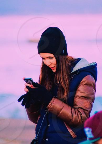 smiling woman in brown and black hoodie wearing black knit cap using iphone near man wearing red cap during daytime photo