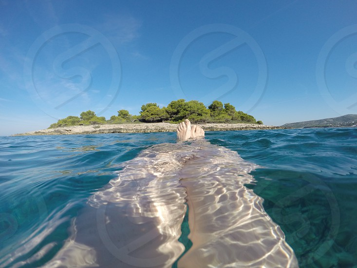 Closeup shot of woman's legs under the sea with little island on the horizon photo