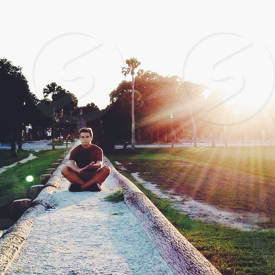 man in burgundy t shirt in drain in lotus position photo