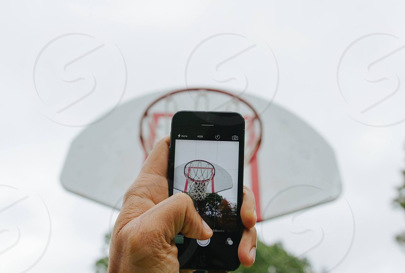 person taking photo of basketball ring photo